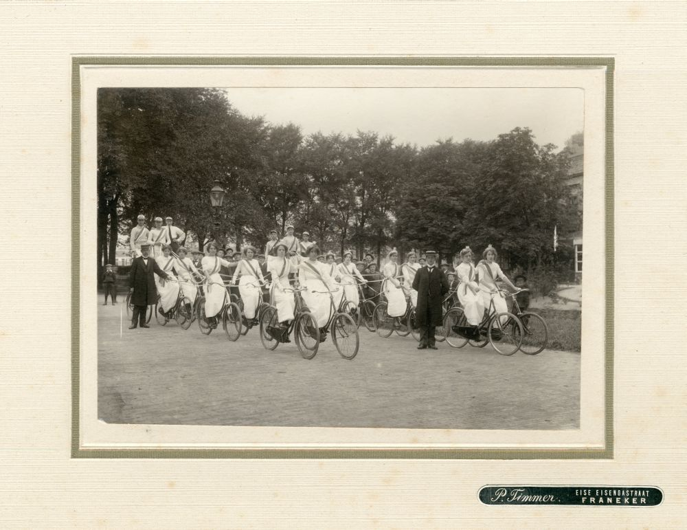 Foto in zwart-wit van een groep meisjes op fietsen die linten vasthouden in Franeker door P. Timmer