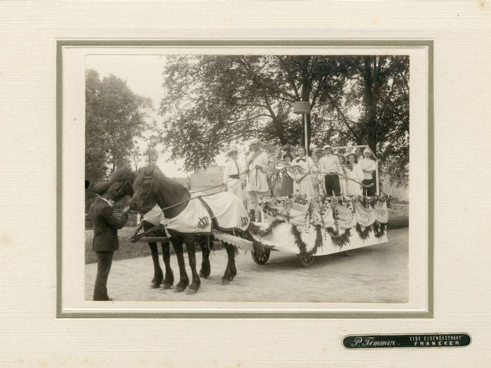 Foto in zwart-wit van een groep jongens en meisjes met sportattributen op een praalwagen in Franeker door P. Timmer
