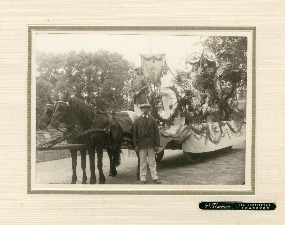 Foto in zwart-wit van een groep jongens en meisjes op een praalwagen van de Nederlandse Kaatsbond in Franeker door P. Timmer