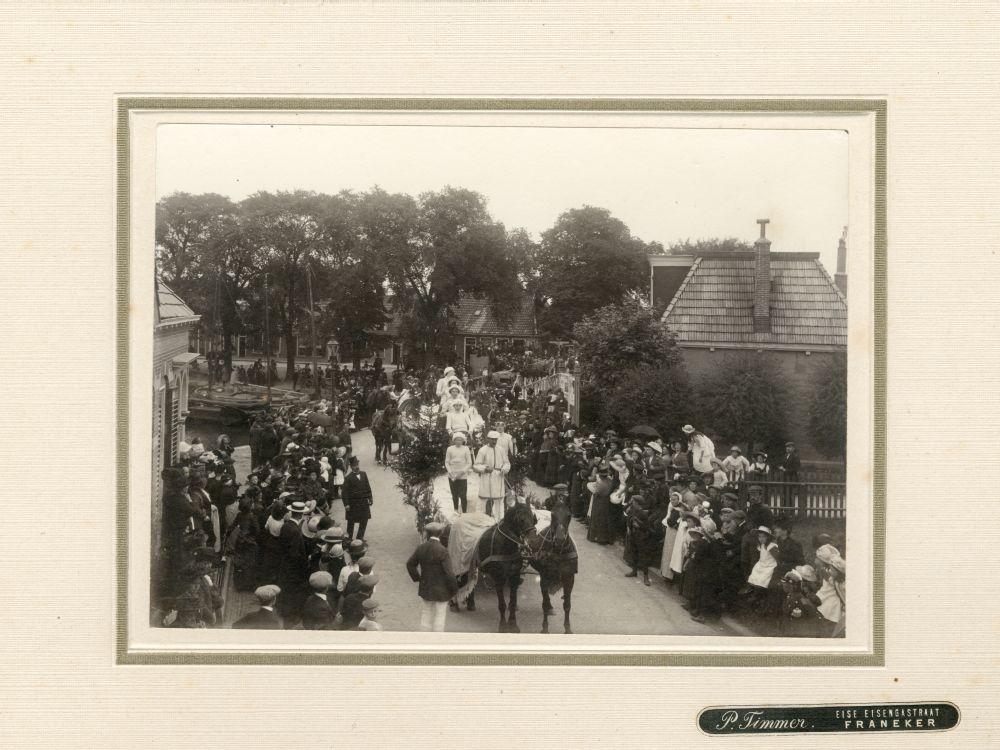 Foto in zwart-wit van een optocht met praalwagens in Franeker door P. Timmer