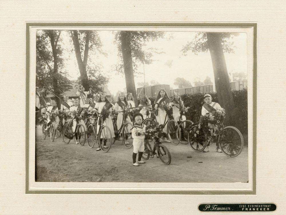 Foto in zwart-wit van een groep jongens en meisjes met versierde fietsen in Franeker door P. Timmer