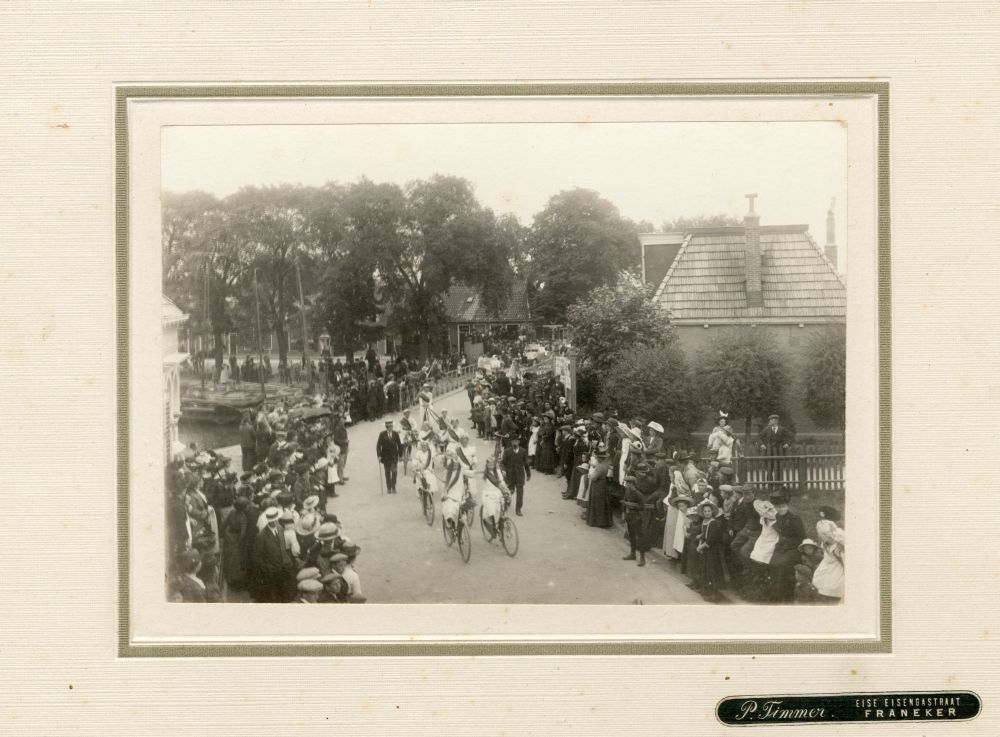 Foto in zwart-wit van een optocht met fietsende meisjes in Franeker door P. Timmer