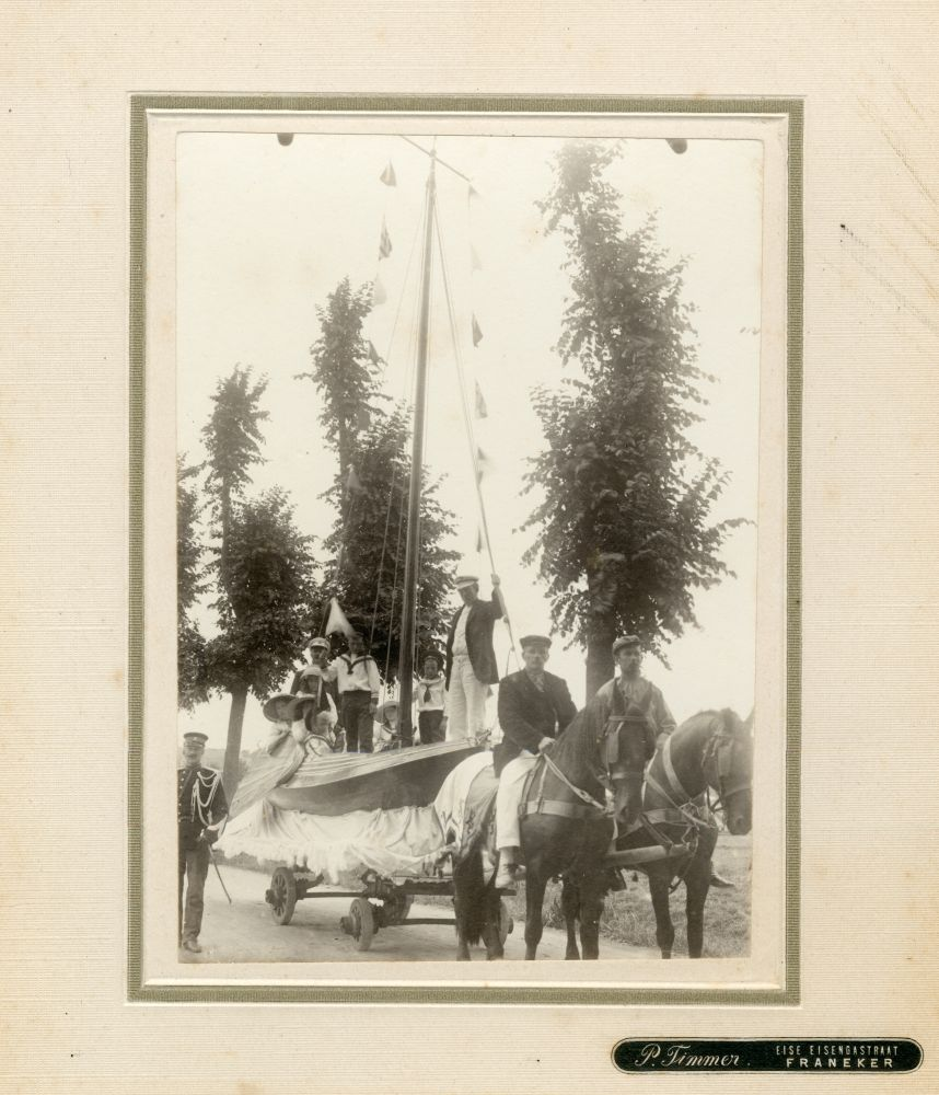 Foto in zwart-wit van een wagen met een tjalkachtige boot in Franeker door P. Timmer