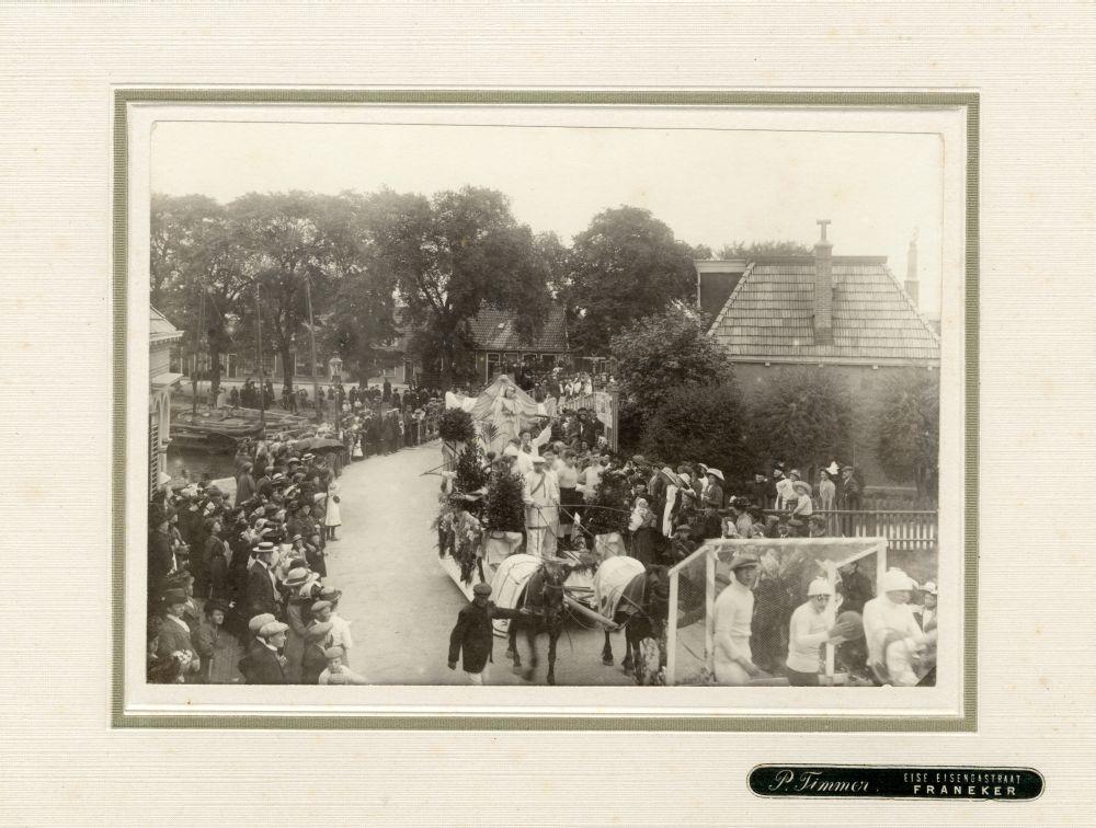 Foto in zwart-wit van een optocht met een praalwagen in Franeker door P. Timmer