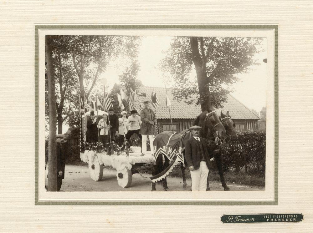 Foto in zwart-wit van een groep mensen op een wagen in Franeker door P. Timmer