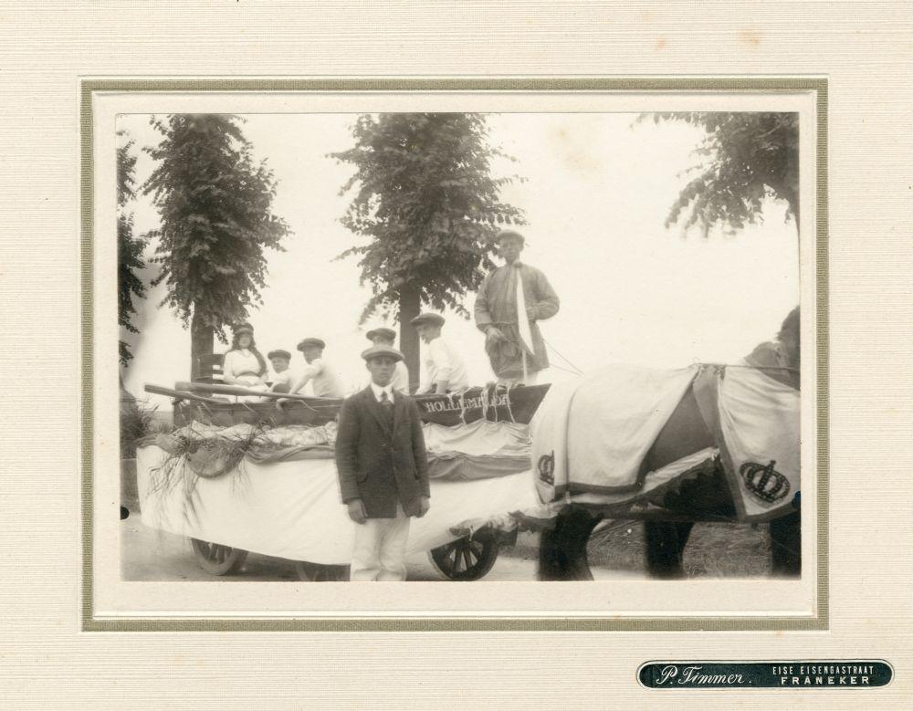 Foto in zwart-wit van jongens en meisjes in een sloep op een wagen in Franeker door P. Timmer
