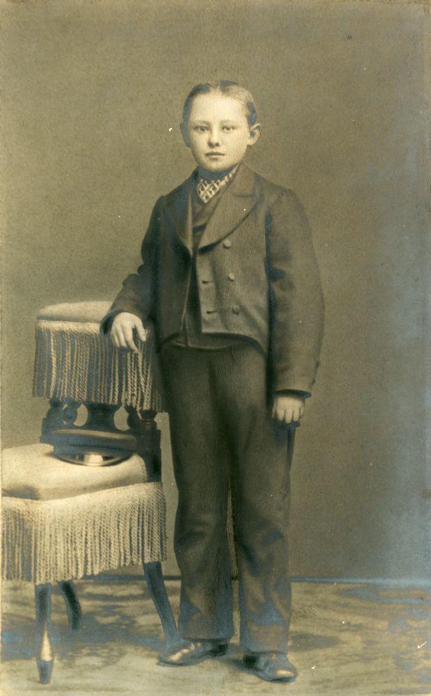 Foto in zwart-wit van een jongen in net kostuum