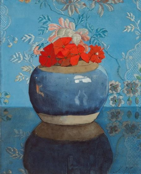 Rode geraniums in blauwe gemberpot tegen geborduurde lap.