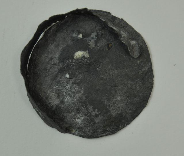 Tinnen deksel, fragment. (Afkomstig van een kaartenkoker ?). Afkomstig uit het VOC-schip 'Geldermalsen', vergaan in 1752.